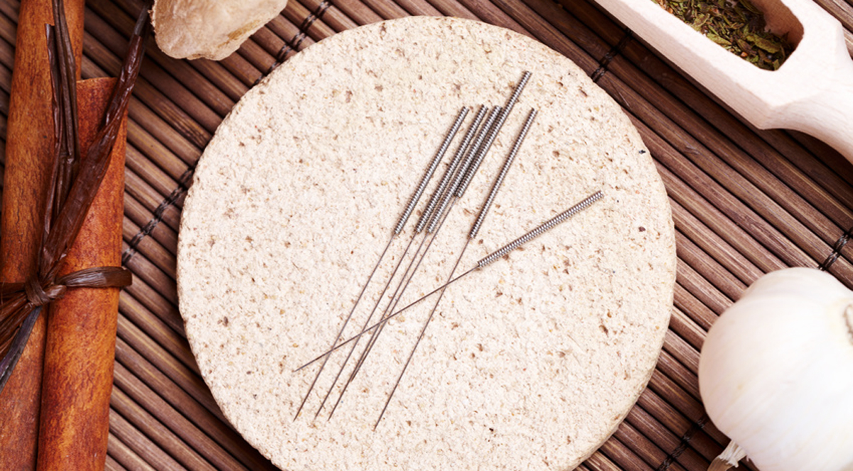 Acupuncture needles laying on the stone mat and herbs like garlic. TCM Traditional Chinese Medicine concept photo